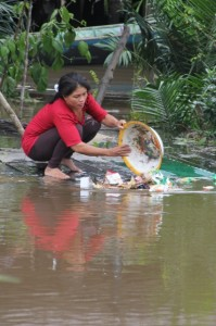 and this is how it gets into the water: woman emptying the rubbish bin in Macong