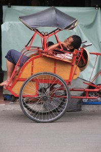 becak driver resting, inside his own becak