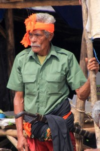 another man, traditionally dressed with headband, sarong and machete