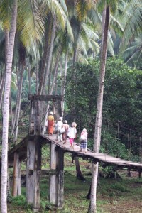 Batak people crossing a suspension bridge in Sumatra