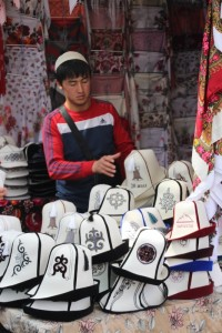 young man selling the typical Kyrgyz felt hats