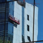 construction mirrored in modern glass office building in Almaty
