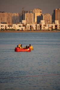 paddling on the artificial lake, surrounded by a construction boom