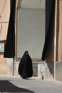 woman passing a mosque decorated with black flags for Moharram