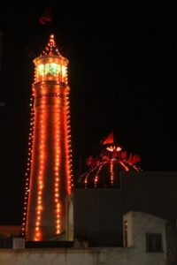 mosque decorated with lights along the minaret and the cupola