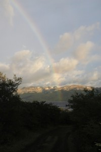 a rainbow over the lake: that means that it rains, somewhere