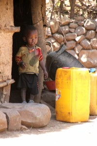 young boy contemplating the size of the water container