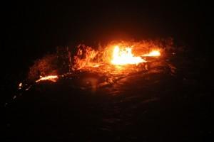 an explosion illuminates the crater floor