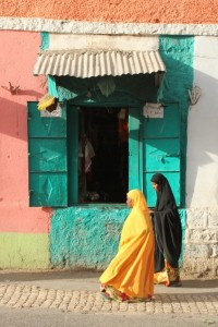 colourful women passing a colourful shop
