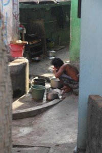 a man washing the dishes in his courtyard