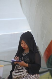 a young woman making notes in front of one of the wooden ships
