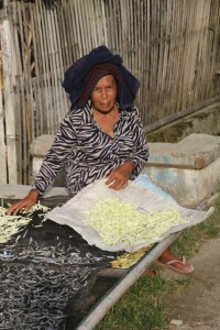 woman handling simultanuously coconut scrapes and dried fish, mmm