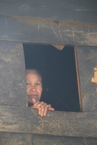 Mamasa lady spying from the window of a traditional house