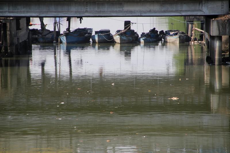small boats moored under a bridge