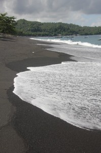 the black beach, stretching along the wide bay