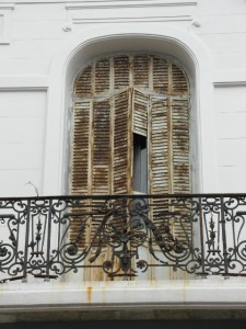 and one of its typical balconies in front of shuttered windows