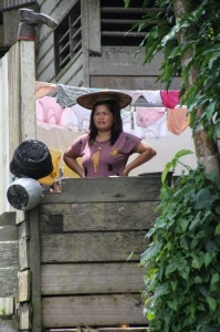 one of the villagers observes the river activities from her balcony