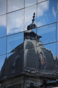 the CEC Bank Palace mirrored in the windows of the Bucharest Financial Plaze