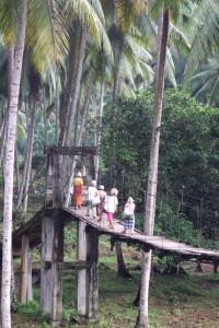 Batak people crossing a suspension bridge in Sumatra