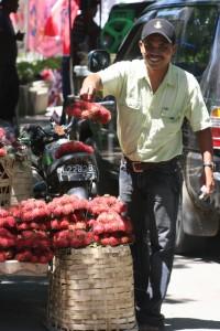 proudly selling rambotan, tropical fruit
