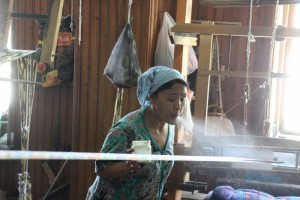 one of the weavers spreaying starch across the weaving, part of the process