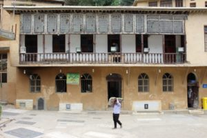 a village building next to the mosque, with balconies and stained glass windows