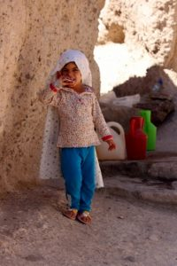 young girl in front of het cave house in Meymand