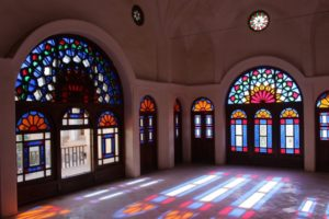 large room, decorated with stained glass reflecting on the floor, in the Khan-e Tabatabei