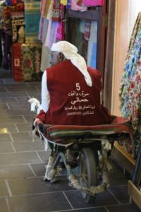 a porter in the souq, finding alternative use for his wheel barrow