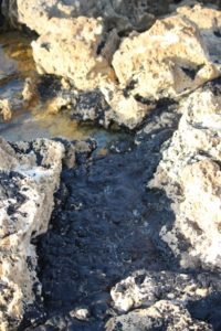 oil spilled in between the rocks